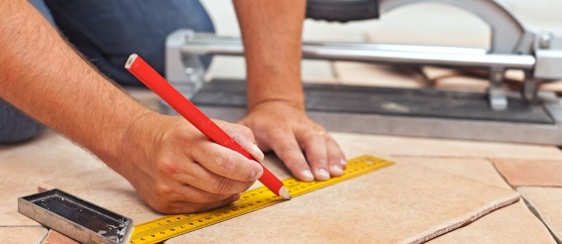 man measuring up a tile